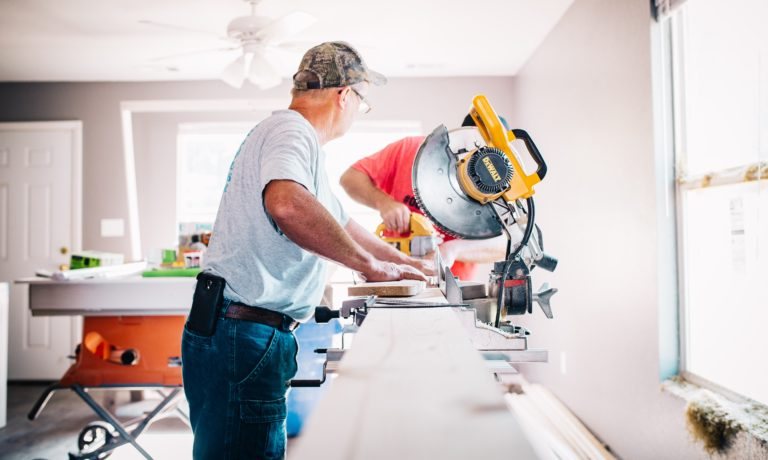 two-men-using-a-saw -to-renovate-their-edmonton-home-in-the-winter