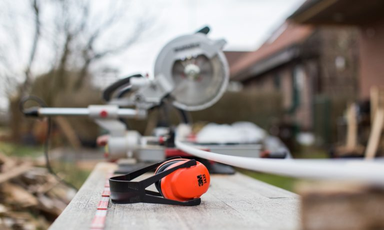 ear-muffs-sitting-by-a-saw-by-an-edmonton-home-that-is-being-renovated