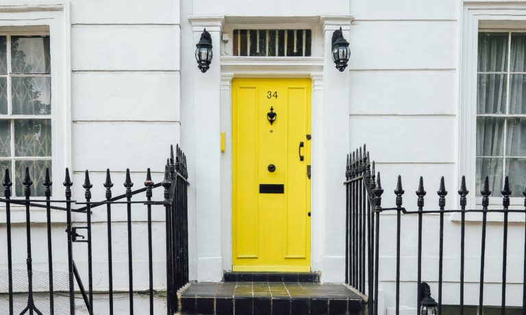 a-yellow-door-raising-the-curb-appeal-on-a-white-house