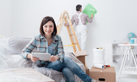 a-contractor-painting-wall-green-behind-a-women-sitting-on-a-couch-wondering-where-to-start-her-home-renovation-in-edmonton