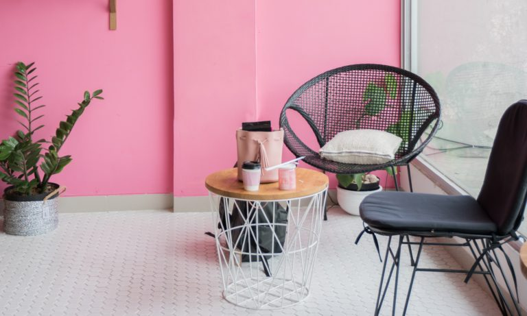 chair-sitting-in-front-of-a-pink-home-feature-wall