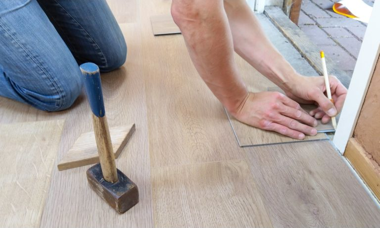 hands and knees of carpenter are visible as they measure door frame for flooring. pencil is in hand and hammer is nearby.